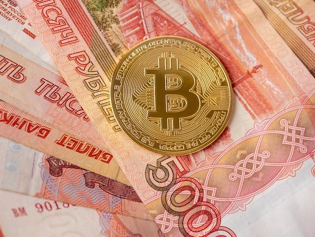 Moneta bitcoin leży na tle rubli rosyjskich. kopanie kryptowalut i koncepcja wydobycia. widok z góry, układ płaski.