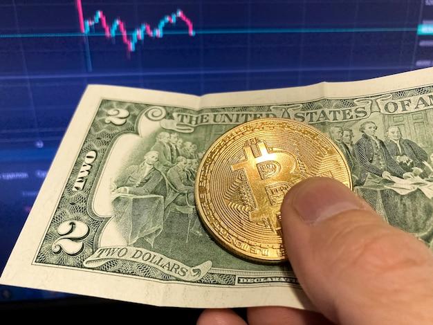 Moneta bitcoin na papierowym rachunku dwa dolary. selektywne skupienie. elektroniczny harmonogram bitcoinów, transakcje wolumenowe