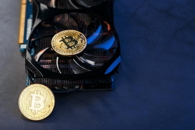 Moneta bitcoin na potężnej karcie graficznej do kopania i zarabiania koncepcji kryptowaluty na ciemnej powierzchni