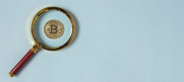 Moneta bitcoin przez lupę na niebieskim tle