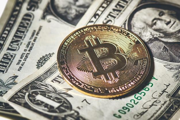 Moneta bitcoin spoczywająca na banknotach dolarowych