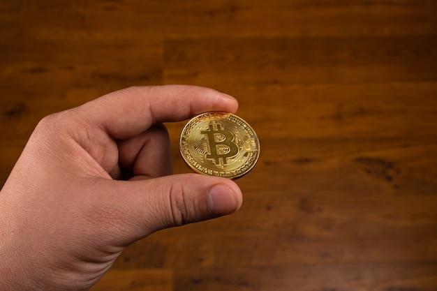 Moneta bitcoin w ręku, kryptowaluta btc z bliska.
