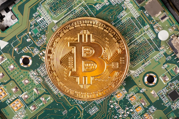 Moneta bitcoin z bliska na tle płyty głównej.
