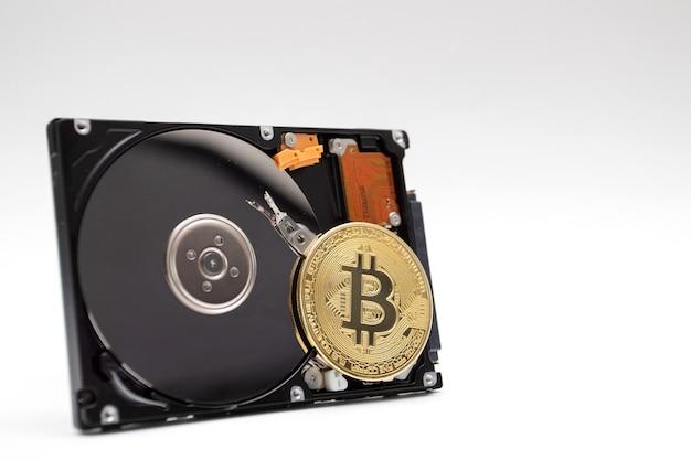 Moneta bitcoina z dyskiem twardym. kopanie monety kryptowaluty na dysku twardym.