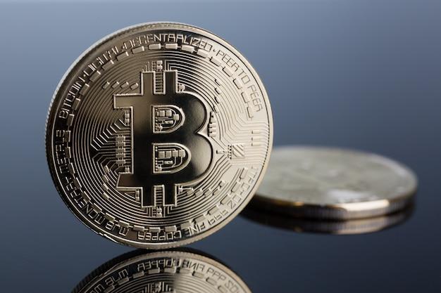Moneta bitcoinów kryptowalutowych na szaro-niebieskim
