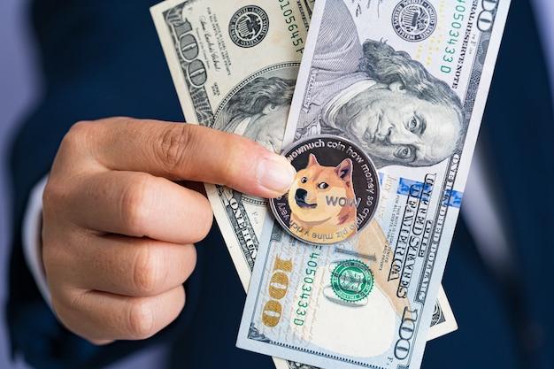 Moneta dogecoin doge dołączone do kryptowaluty i stosu 100 nowych dolarów amerykańskich pieniądze american na rękę człowiek biznesu ubrany w niebieski garnitur w kieszeni. zarchiwizuj i włóż i daj mi.