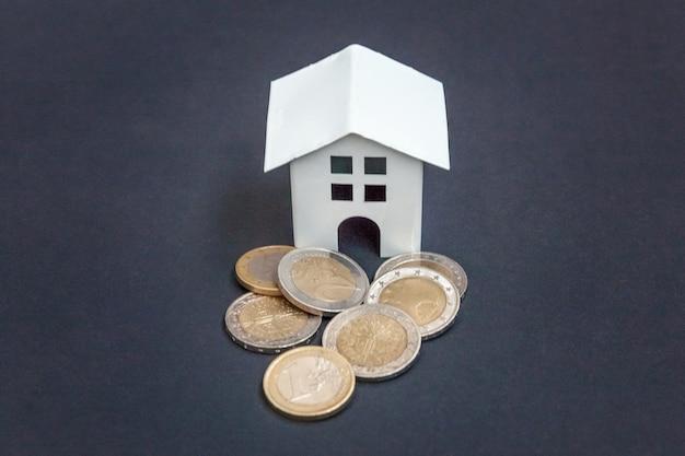 Moneta euro i symboliczny mały domek z zabawkami