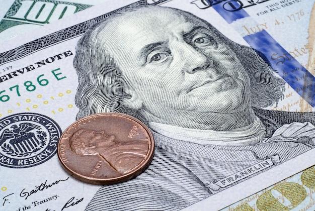 Moneta jeden cent na banknocie stu dolarów zbliżenia