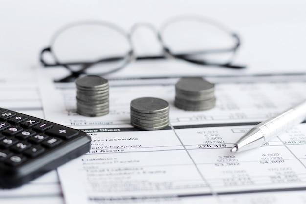 Moneta, kalkulator, długopis na papierach służbowych