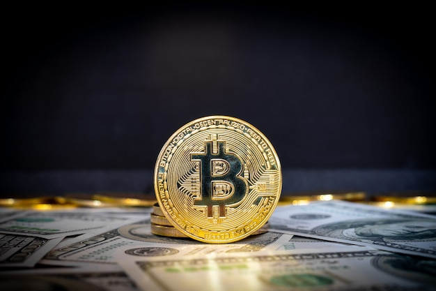 Moneta kryptowaluty bitcoin i banknoty dolarowe w tle
