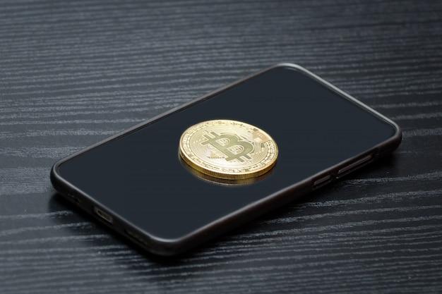 Moneta kryptowaluty bitcoin w telefonie. czarny drewniany stół