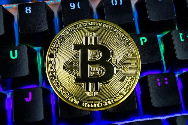 Moneta kryptowaluty bitcoin zbliżenie kolorowej klawiatury.