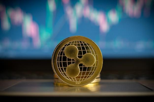 Moneta kryptowaluty i wykres finansowy w tle