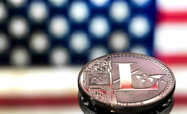 Moneta litecoin na tle flagi amerykańskiej, pojęcie wirtualnych pieniędzy, zbliżenie.