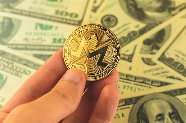 Moneta monero w ręku na tle banknotów dolarowych, zdjęcie koncepcji handlu i wymiany