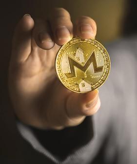 Moneta monero w zbliżeniu ręki, zdjęcie tła biznesowego kryptowaluty
