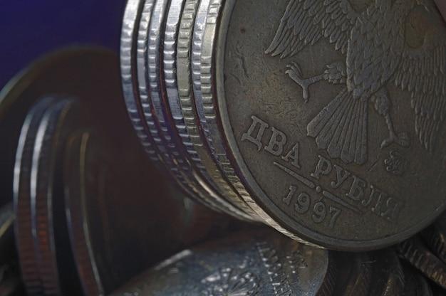 Moneta rosyjska o nominale 10 rubli (rewers) na tle innych monet składanych w kolumny.