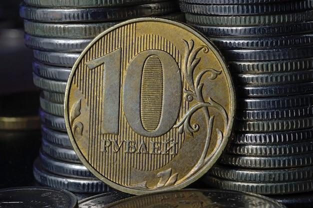 Moneta rosyjska o nominale 10 rubli (rewers) na tle innych monet złożonych w kolumnach.