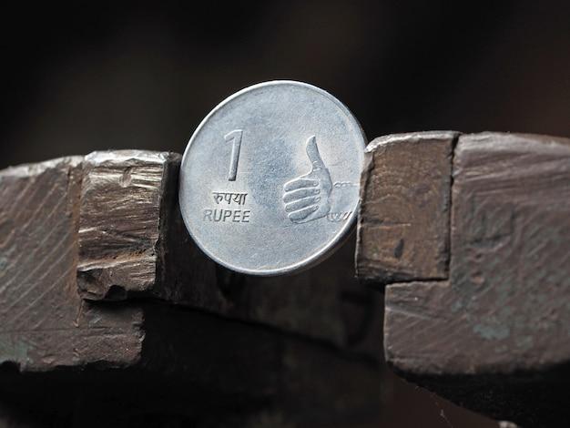 Moneta rupia indyjska zaciśnięta z obu stron w metalowym imadle. pojęcie presji finansowej na biznes walutowy