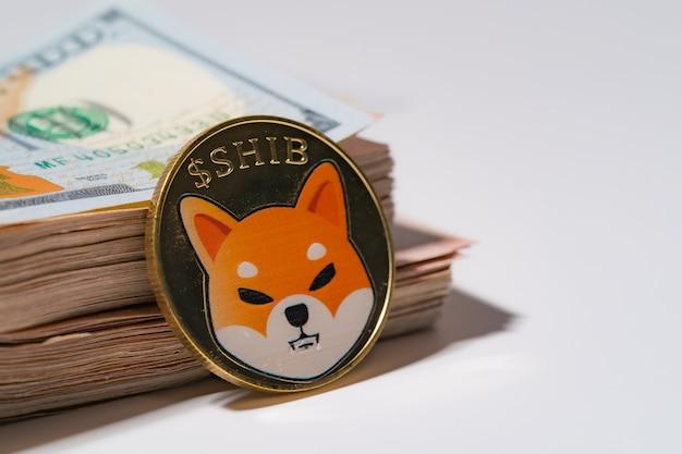 Moneta shiba dołączone do monety kryptowaluty na stosie 100 nowych dolarów amerykańskich pieniądze american wirtualny blockchain przyszłości technologii jest koncepcja pieniędzy zamknij się i makro na białym tle.