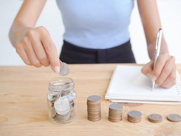 Moneta w słoiku i stos gotówki na drewnie z rozmyciem obrazu szczupłej i opalonej kobiety piszącej plan oszczędzania pieniędzy