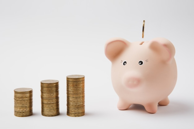 Moneta wpadająca do różowej skarbonki, stosy złotych monet na białym tle. pieniądze akumulacji bankowości inwestycyjnej lub koncepcji bogactwa usług biznesowych. skopiuj makiety reklamowe.