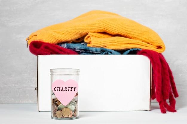 Monety, banknoty w słoiku pieniędzy i pudełko z darowizn
