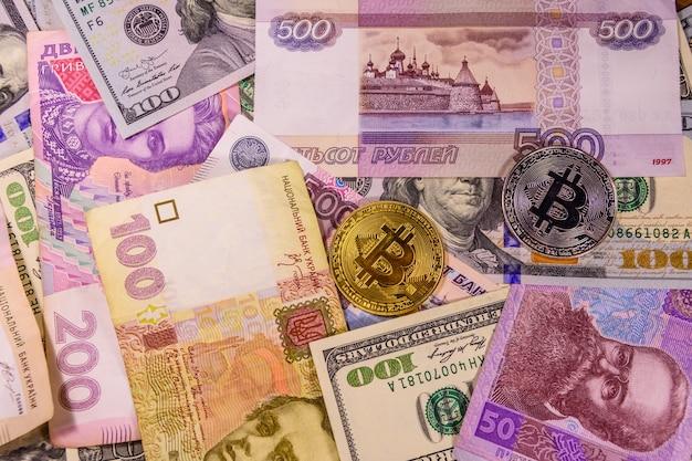 Monety bitcoin na banknotach amerykańskich, ukraińskich i rosyjskich
