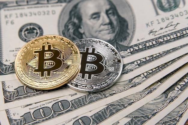 Monety bitcoin na banknotach dolara amerykańskiego.