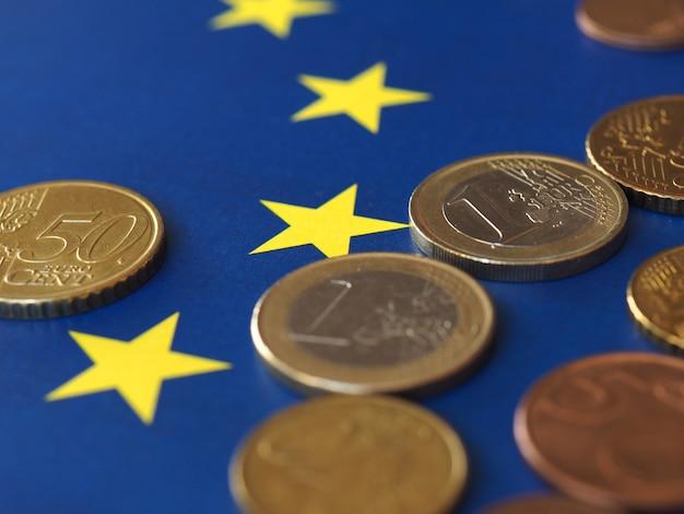 Monety euro (eur), waluta unii europejskiej nad flagą europy