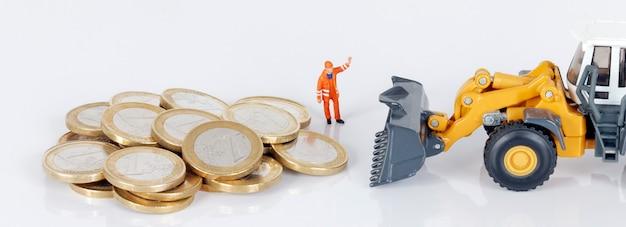 Monety euro pieniądze z koparką i pracownikiem na białym tle