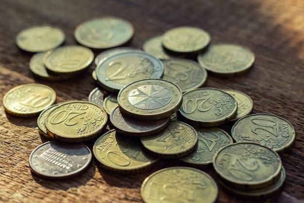 Monety euro stosu paczki rozsypiska sterta na drewnianym w ciemnych kolorach.