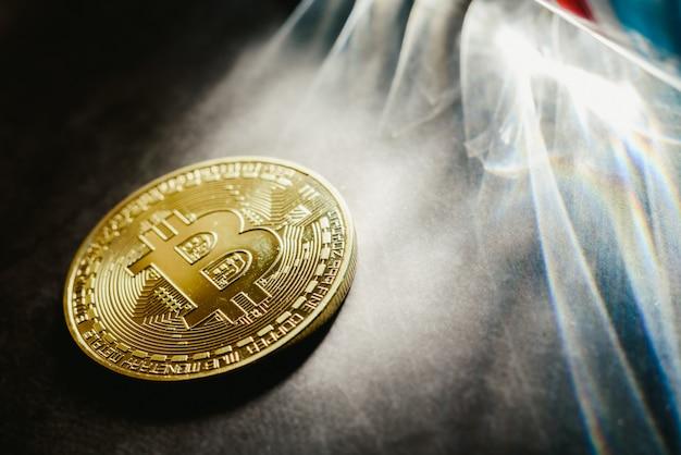 Monety fizyczne bitcoin oświetlone promieniami światła z ciemnym tłem.