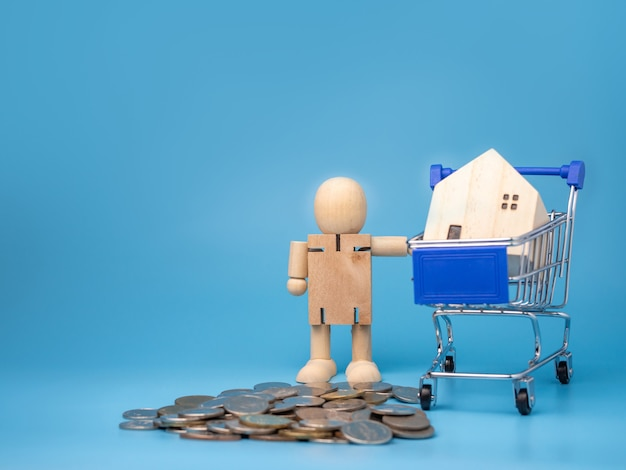 Monety i drewniane lalki, które stoją obok koszyka z modelowym drewnianym domkiem na niebiesko