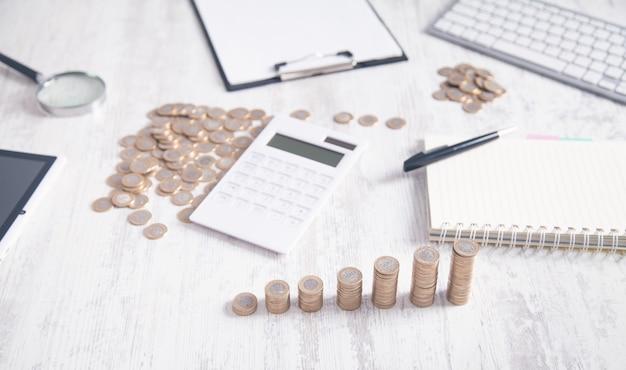 Monety i kalkulator na biurku biznesowym.