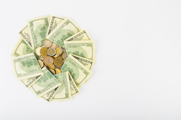 Monety i papierowy pieniądze na białym tle