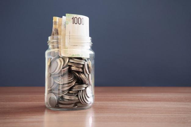 Monety i pieniądze w szklanym słoju na ciemnym tle. koncepcja inwestycji. wzrost gospodarczy. zarządzanie biznesem. akumulacja kapitału. skopiuj miejsce.