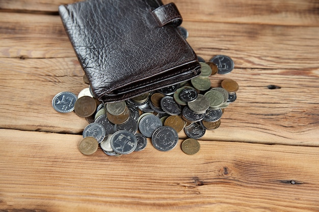 Monety i portfel na drewnianym stole