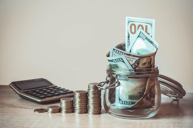 Monety kalkulator stosu i banknoty dolarowe w szklanym słoju koncepcja oszczędzania pieniędzy finansowych