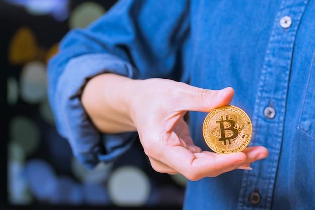 Monety kryptowalut - bitcoin. kobiety trzymają pod ręką monetę kryptowalutową