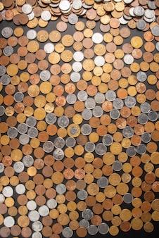 Monety, monety brazylijskie o różnej wartości rozłożone na czarnej skórzanej powierzchni, widok z góry.