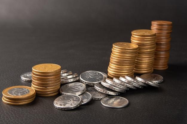 Monety, monety brazylijskie różnej wartości… ułożone na czarnej skórze, selektywne skupienie.