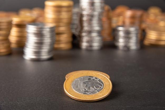 Monety, monety brazylijskie w różnych ilościach ułożone w stos i jedna prawdziwa moneta na pierwszym planie na czarnej skórze, selektywne ogniskowanie.