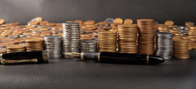 Monety, monety brazylijskie w różnych ilościach ułożone w stos i wieczne pióro na czarnej skórze, selektywne ogniskowanie.