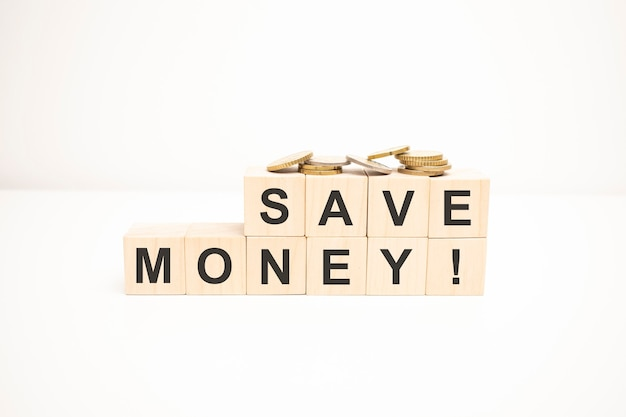 Monety na schodach stosu jako krok rosnącego wzrostu i drewnianego bloku kostki ze słowem oszczędzają pieniądze. koncepcja rocznego budżetu pieniędzy