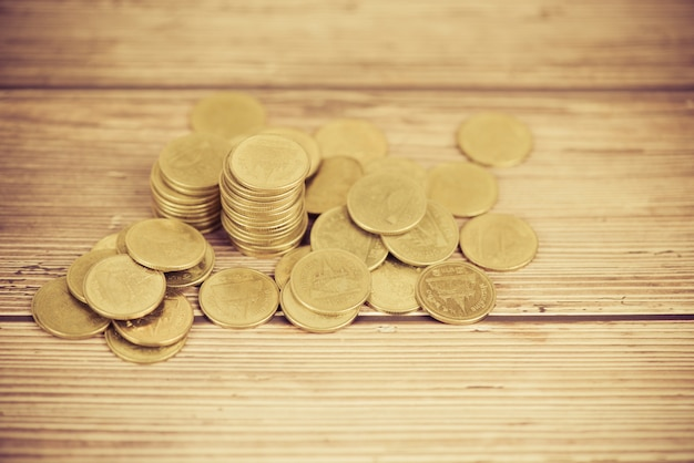 Monety na stole stos złote monety na drewniane pieniądze finansowe