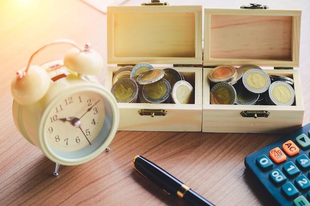 Monety na stole w jego biurze w finansach, inwestyci, oszczędzania i bankowości pojęciu ,.