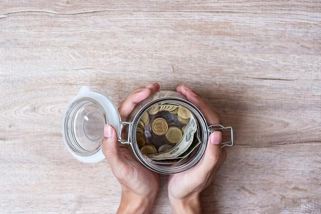 Monety pieniądze w szklanym słoju. światowy dzień oszczędzania, biznes, inwestycje, planowanie emerytalne