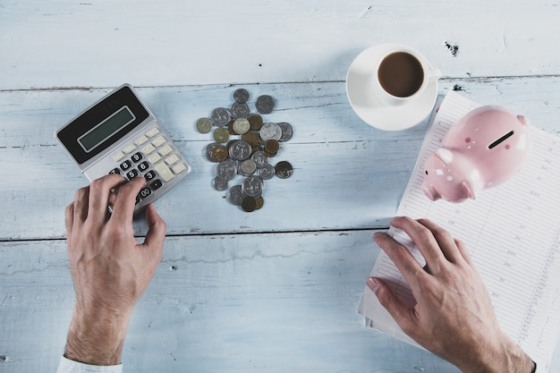 Monety ręki człowieka i skarbonka z kalkulatorem na stole
