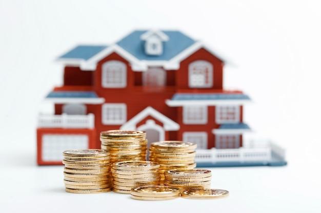 Monety rmb ułożone przed modelem mieszkaniowym (ceny domów, kupno domu, nieruchomość, koncepcja hipoteczna)